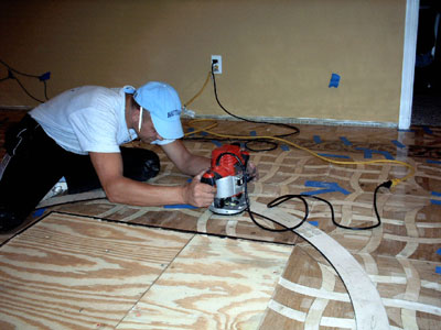 Using router  and template the floor is cut to fit the wood floor medallion