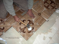 Tapping parquet tiles to insure  adhesion